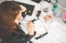 Aerial view of a young woman with brown hair contemplating her revolving utilization. She has a pen in her mouth and an open notebook on her desk.