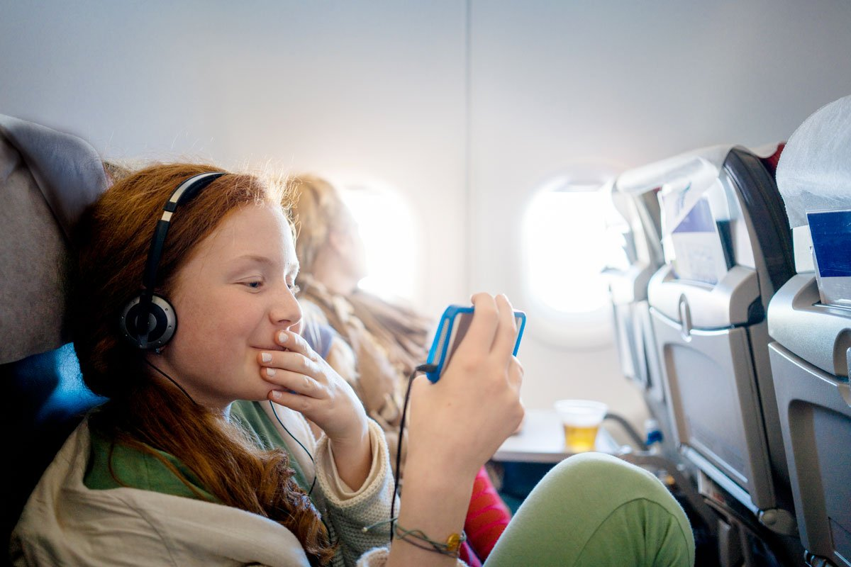 A young girl watches a movie on her iPhone on a plane.
